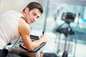 smiling fitness man at legs muscles exercises with bicycle training machine station in gym