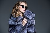 A close up portrait of a beautiful woman wearing a fur coat with hood and sunglasses. Beauty, winter poster