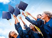 stock photo of graduation hat  - Students throwing graduation hats in the air celebrating - JPG