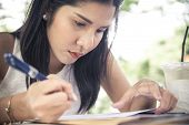 Young Woman Concentrate Reading Book. Girl Learning Writing Homework. Education Assessment Concept.  poster