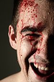Close up of handsome laughing man face in blood