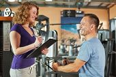 Man exercising on cable machine in gym and listening to female fitness trainer