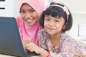 stock photo of muslim kids  - Southeast Asian children surfing internet at home - JPG