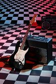 Guitar and sound amplifying equipment on checkerboard background with red lighting.