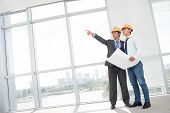 stock photo of premises  - Tilted image of two supervisors comparing blueprint with actual building interior - JPG