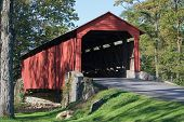 stock photo of covered bridge  - A rustic Lancaster County Pennsylvania covered bridge open to vehicle traffic - JPG
