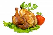 Roasted whole chicken on lettuce leaf with vegetables
