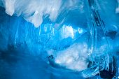 stock photo of cave  - blue ice cave covered with snow and flooded with light - JPG