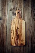 Olive wood cutting board on rustic background