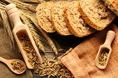 stock photo of food crops  - Rye spikelets and bread on wooden background - JPG