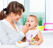 foto of feeding  - Mother Feeding Her Baby Girl with a Spoon - JPG