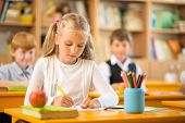 stock photo of schoolgirls  - Little schoolgirl sitting behind school desk during lesson in school - JPG