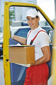 Postal delivery courier man in front of cargo van delivering package carton box