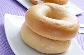 some plain bagels in a plate on a set table with a violet tablecloth