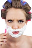 image of razor  - Serious model in hair curlers posing with shaving foam and razor on white background - JPG