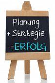 Planning strategy written on blackboard in german on white background