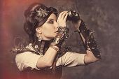 image of steampunk  - Portrait of a beautiful steampunk woman looking through the binoculars over grunge background - JPG