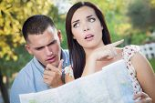Lost and Confused Mixed Race Couple Looking Over A Map Outside Together.