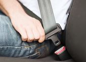 transportation and vehicle concept - man fastening seat belt in car