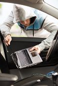 transportation, crime and ownership concept - thief stealing laptop from the car