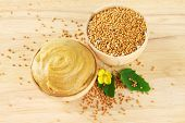 picture of mustard seeds  - Mustard with seeds and mustard flower on wooden background - JPG