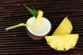 Pina colada drink in coconut, on bamboo mat background