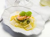 pesto ravioli with shrimp and parmesan flakes
