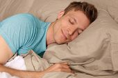 image of laying-in-bed  - Young man peacefully sleeping in bed - JPG
