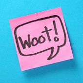 stock photo of jargon  - The word Woot written inside a speech bubble on pink sticky note attached to a blue paper background - JPG
