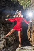 image of mini dress  - Young fashion blonde woman posing in red mini dress in front of stone background - JPG