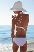 stock photo of sun tan lotion  - Tanning lotion in the shape of sun on woman - JPG