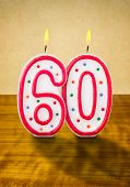 Burning birthday candles number 60 on a wooden background