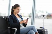 image of gate  - Airport business woman on smart phone at gate waiting in terminal - JPG