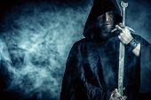 stock photo of sword  - Portrait of a courageous warrior wanderer in a black cloak and sword in hand - JPG