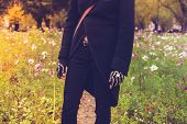Goth Dressed In Black Standing In Meadow