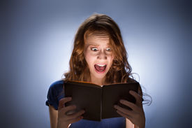 image of horrific  - Concept shot of woman reading horror book nad screaming - JPG