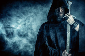 image of sword  - Portrait of a courageous warrior wanderer in a black cloak and sword in hand - JPG