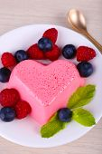 Heart shaped cake with berries on plate on wooden background