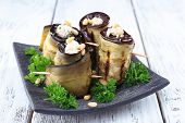 Fried aubergine with cottage cheese and parsley on wooden background