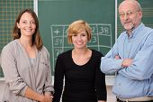 image of work crew  - Group of three school teachers with confident friendly smiles standing in front of a class blackboard one man and two women - JPG