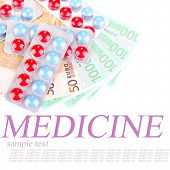Prescription drugs on money background, representing rising health care costs, isolated on white