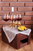Bottle and glasses of wine and cheese on table on brick wall background