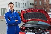 Confident Mechanic With Arms Crossed Standing By Car