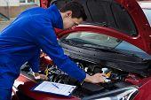 Mechanic In Uniform Repairing Car