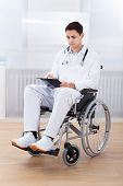 Doctor Witting On Clipboard While Sitting On Wheelchair