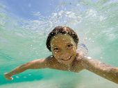 Young boy swimming underwater in tropical sea