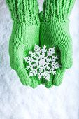 Woman hands in light green knitted mittens with sparkling wonderful snowflake on a white snow background. Winter and Christmas concept.