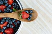 High angel photo of a Strawberry and Blueberries on a wooden spoon laying across a colander full of
