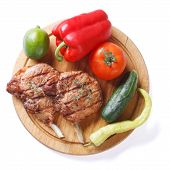 Grilled Pork And Vegetables On A Cutting Board Isolated Top View
