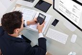 stock photo of angles  - High angle view of businessman calculating tax at desk in office - JPG